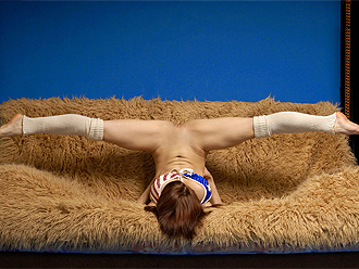 Sexy flexible girl in nude yoga poses on the couch