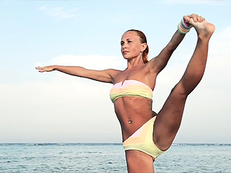 Hot yoga exercises on the ocean shore