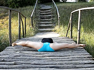 Sexy yoga exercises on a wooden bridge
