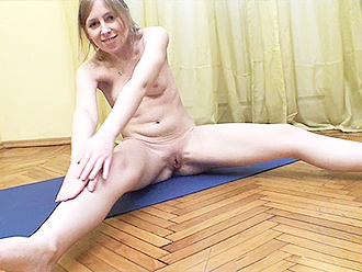 Naked girl stretches out on the yoga mat
