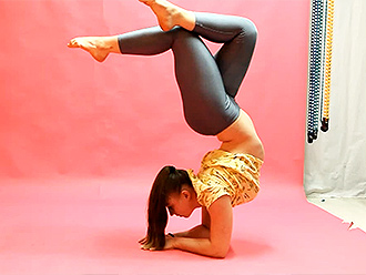Gymnast in yoga pants does exercises in hot yoga video