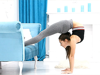 Hot gymnast in tight yoga pants does sexy yoga exercises