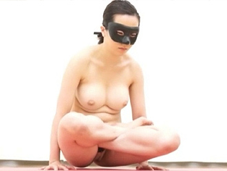 Naked flexible girl in mask performing nude yoga exercises