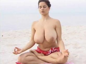 Huge-boobed milf doing nude yoga exercises on a sandy beach