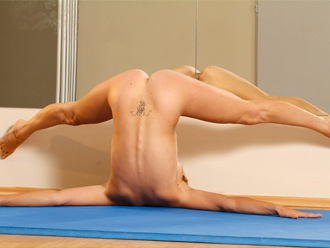 Naked flexible girl does nude yoga exercises on the floor