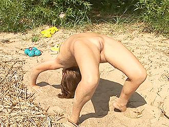 Naked yoga on a sandy beach