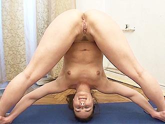 Nude gymnast does naked yoga exercises