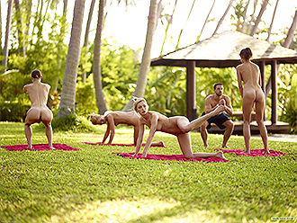 A group of fit naked girls has their nude yoga class in a public park