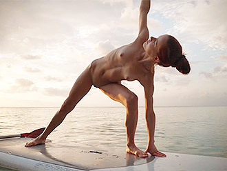 Nude yoga in public beach on the surfboard present you by beautiful and flexible naked girl