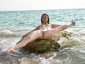 Naked gymnast playing at the public beach preforming nude yoga exercises