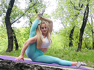 Flexible teen girl demonstrates sexy yoga in public park